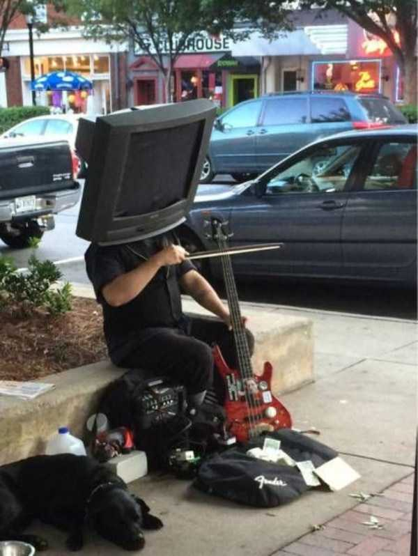 34 - Person with TV on their head playing music in the street.