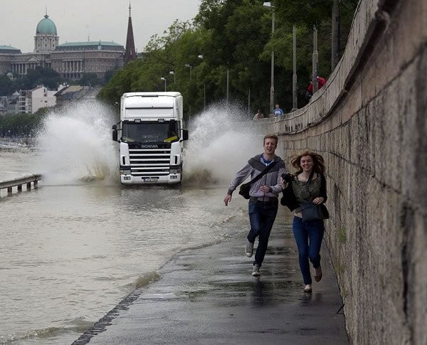 28 - Couple running from truck that is about to splash them with puddle water.