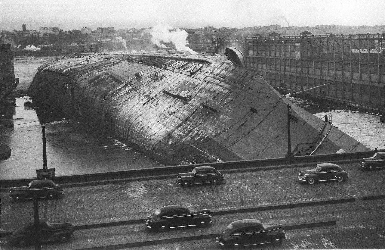 19 - The Normandie (rechristened Lafayette) capsized by the water used to put out an onboard fire, Hudson River Pier, Manhattan, 1942