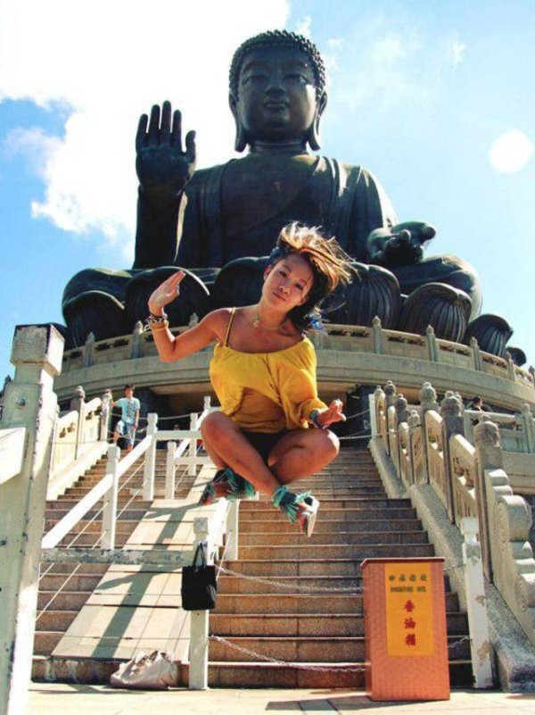 1 - Awesome picture of woman in mid air in front of a Buddhist temple statue.