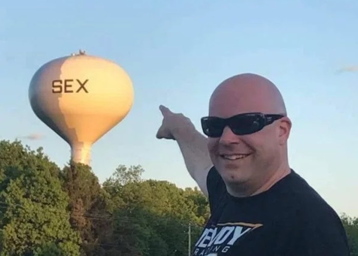 33 - Man pointing at a water tower with a word on it that starts with S