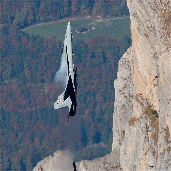 10 - f-15 flying straight upwards right alongside a cliff face.
