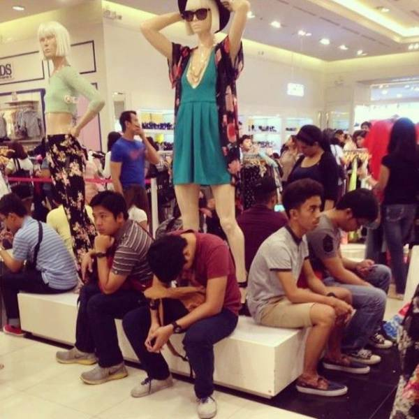 13 - Funny pic of really bored travellers under a mannequin woman.