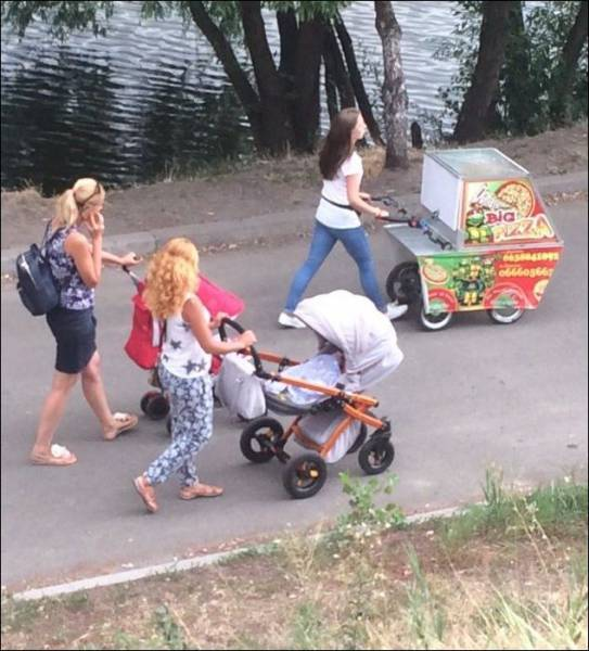 15 - Women pushing their carriages in the park, one of them is not a baby but a pizza wagon.