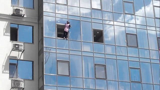 17 - woman casually going out her window of a high-rise building.