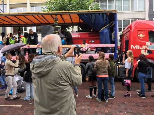 21 - Everyone is taking pics of some street performers on a truck, and old guy is taking pictures of the hot girls.