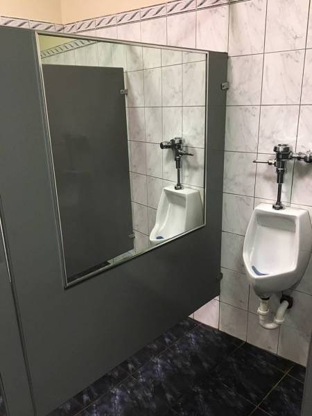 24 - Urinal with massive mirror next to it.