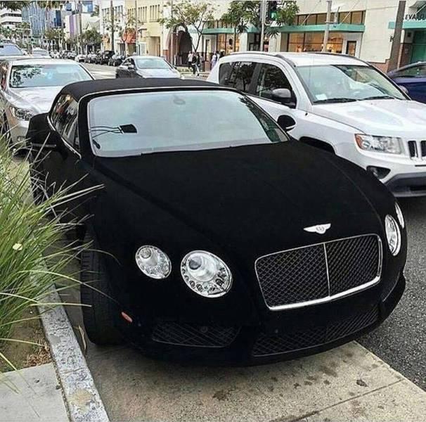 32 - Velvet black Bentley parked on the street.