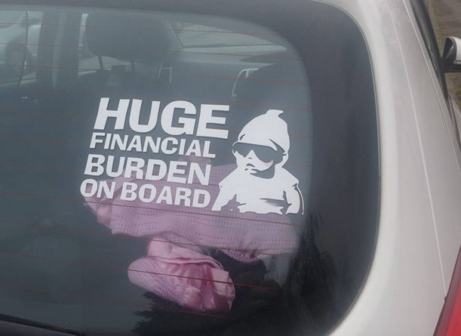 9 - Funny sticker someone put in their car warning that their kid is a huge financial burden.