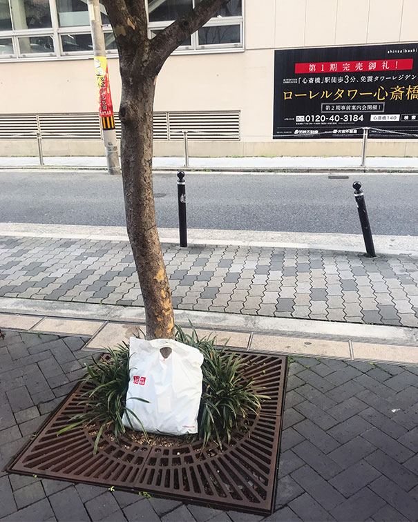 11 - Dropped shopping bag on the streets of Osaka is moved next to a tree untouched.