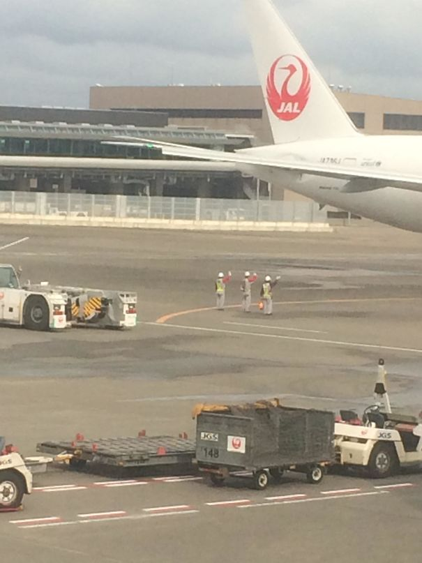 24 - Ground crew waves goodbye to departing plane.