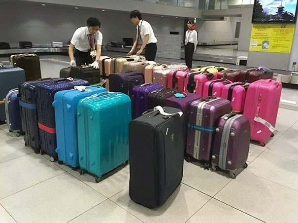 28 - Airport staff sorting luggage by color.