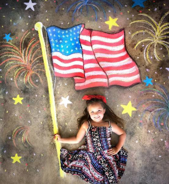 10 - Girl lying down on a chalk outline that makes it look like she is Lady Liberty holding up the flag.