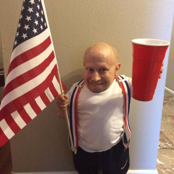 12 - Verne Troyer (mini-me) holding up a large beer cup, an american flag, and red-white-blue suspenders.