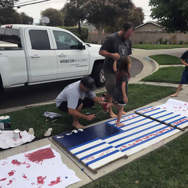 15 - Foot painting flags on the grass, next to large pickup truck.