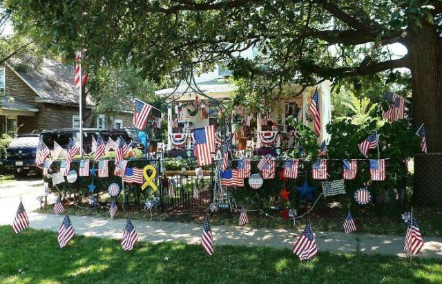 19 - some kind of memorial in front of a house that contains many american flags.