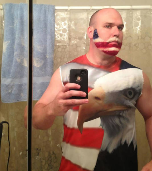 22 - Man wearing a USA flag shirt with a huge bald eagle on it also has an American flag painted beard.