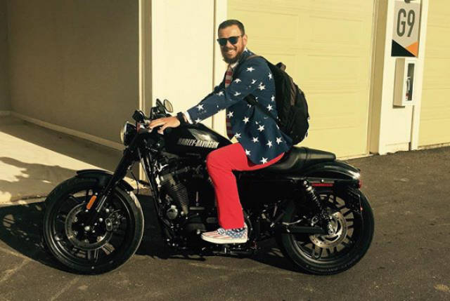 23 - Man wearing red, white, and blue on a motorcycle.