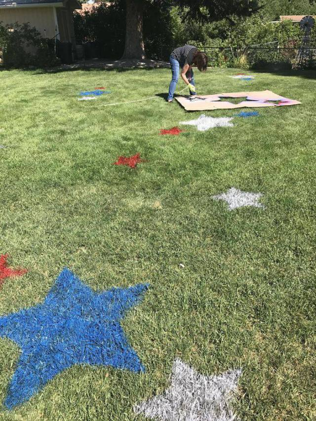 31 - spray painting red, white, and blue stars on the grass.
