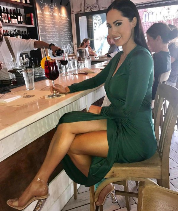 1 - cute girl at the bar having a drink with empty seat next to her