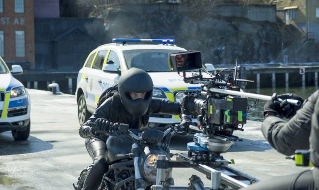 12 - movie set photo of many cameras on a motorcycle rider and police cars in the background
