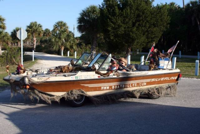 14 - boat that looks like a car with wheels that is driving on the road