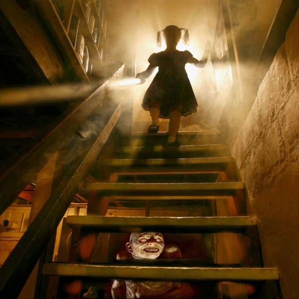 19 - creepy cursed picture of a girl coming down the stairs with light behind her and a poster of Pennywise from IT or some other clown on a poster beyond the stairs
