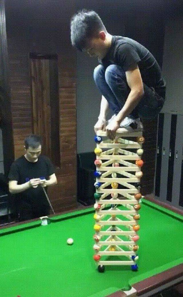 28 - kid standing on top of stacked balls and pool triangles as setup for a trick-shot to replace the bottom 8 ball with some force