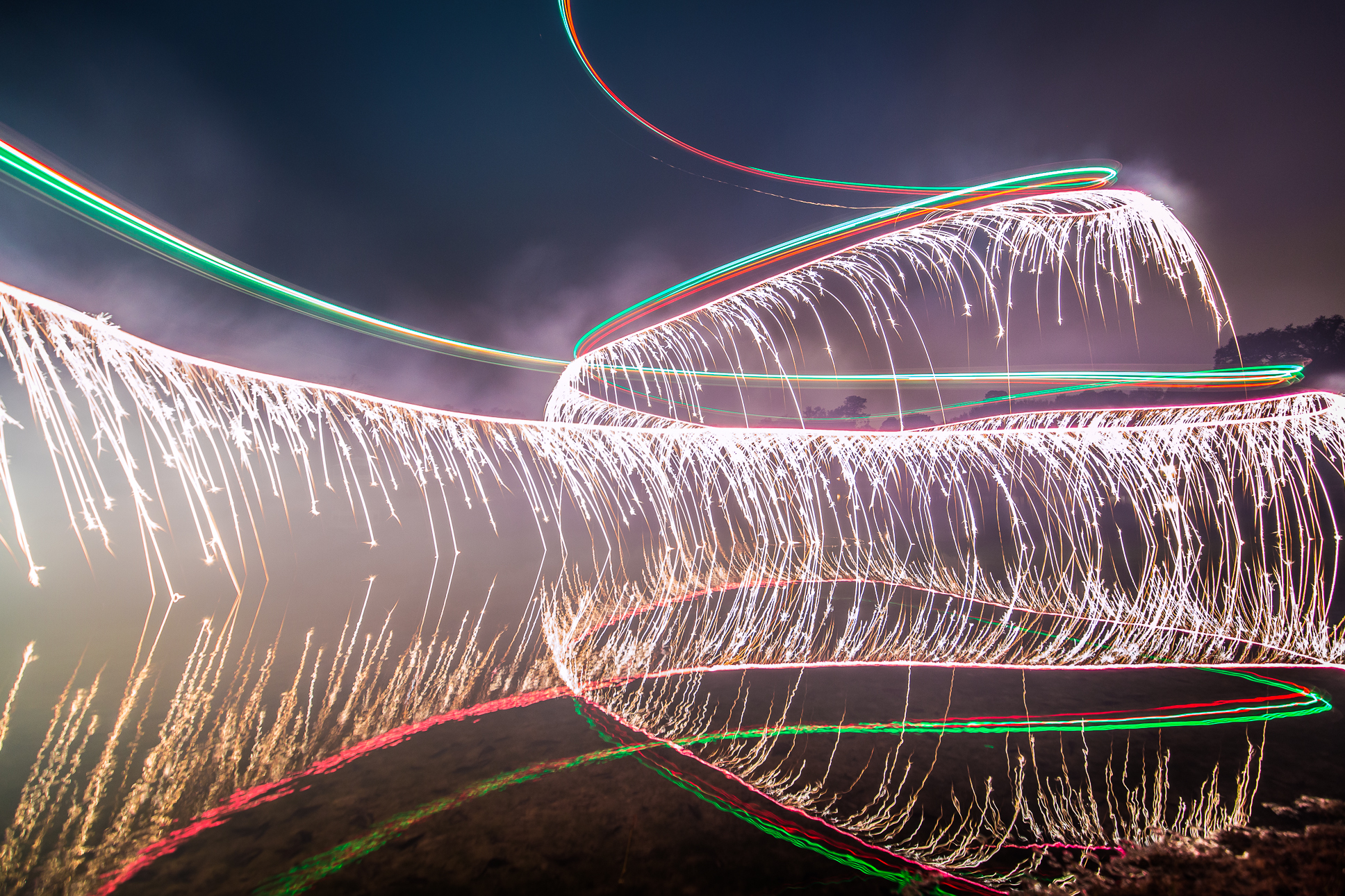 16 - Long exposure photo of a drone flying around with fireworks attached underneath