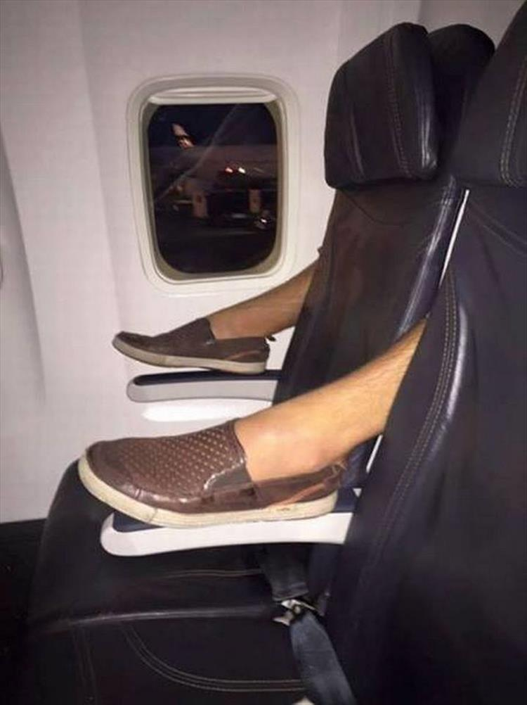 23 - Airplane seat with the feet of the person behind it sticking through in a very rude way.
