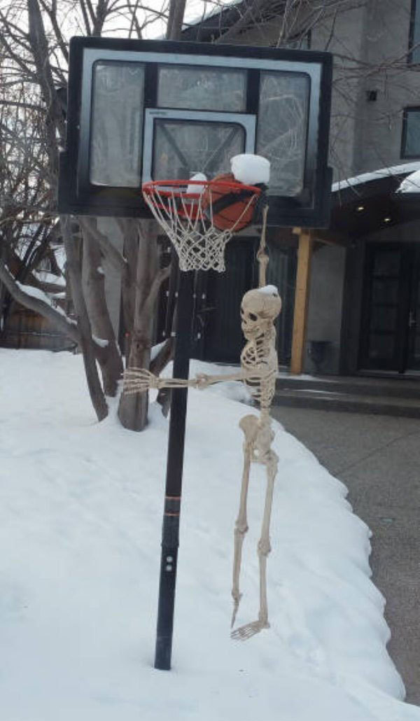1 - A skeleton hanging from a basketball hoop so it looks like it's dunking