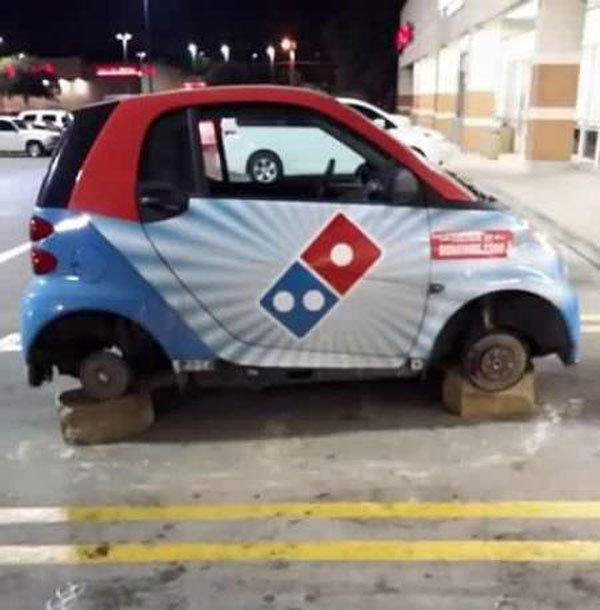4 - Dominoes Pizza delivery car on blocks because it's wheels were stolen