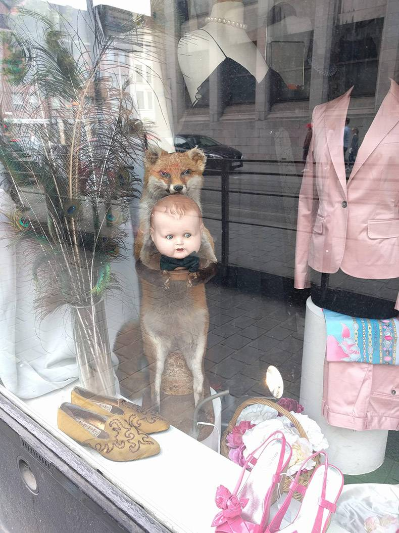 4 - Strange scene in a window of a fox holding a baby in the display case.