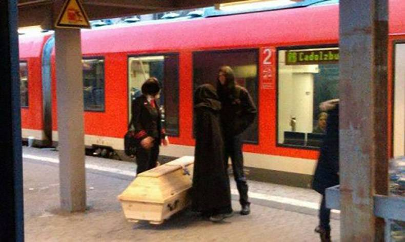 7 - Dark looking crew with a white coffin about to get on the subway.