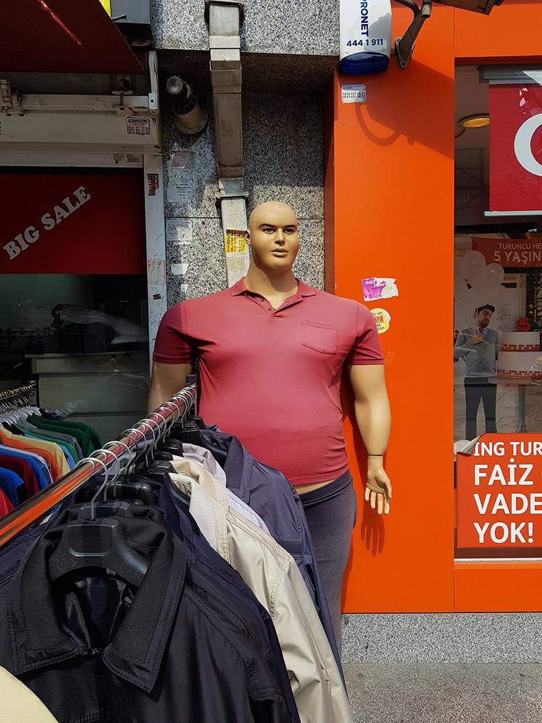26 - Very wide and large mannequin man in a store.