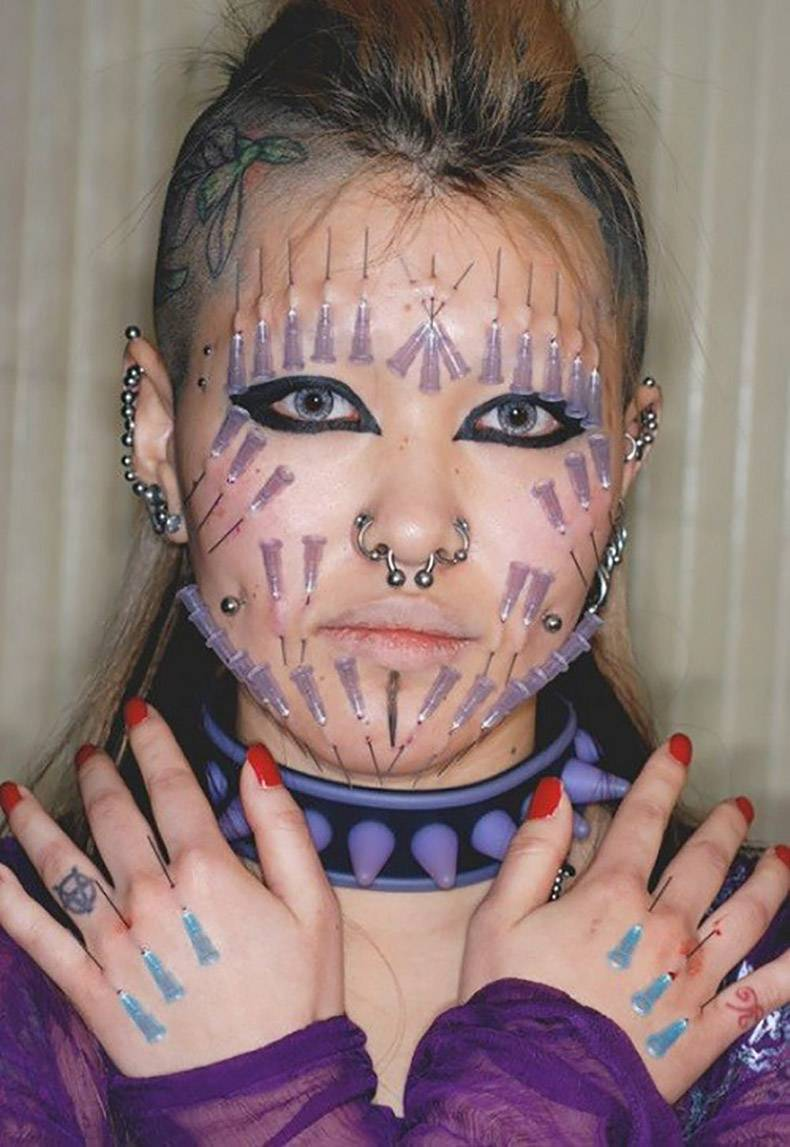 4 - Picture of a girl with piercings and many medical needles stuck into her face and hands.