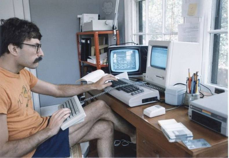 13 - Classic picture of someone with multiple computer screens and keyboards from 80's era computers and hairstyles.