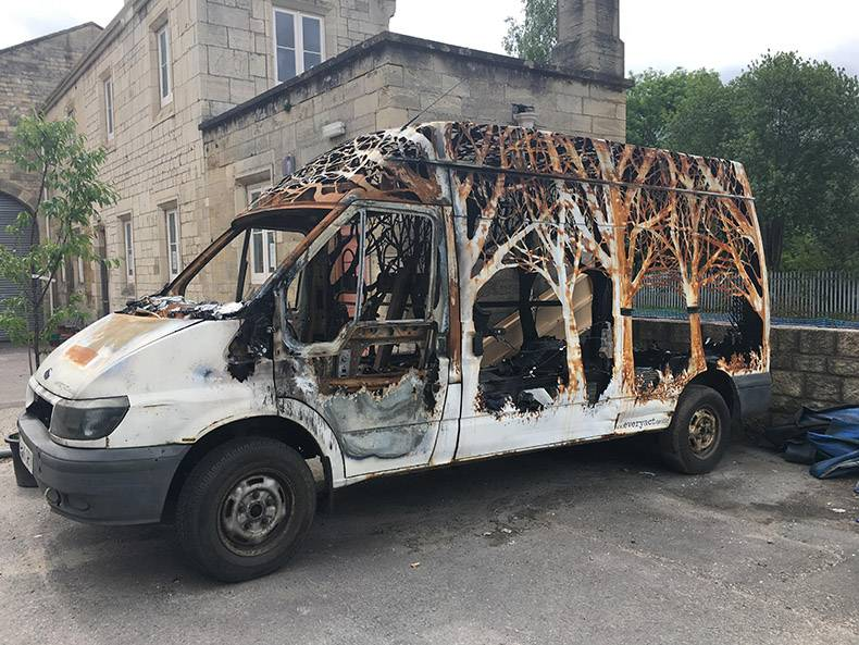 25 - Burnt out van with trees cut into the remaining shell of the vehicle.