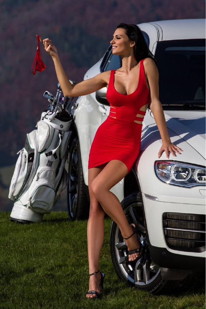 21 - women in red dress on the golf course next to BMW