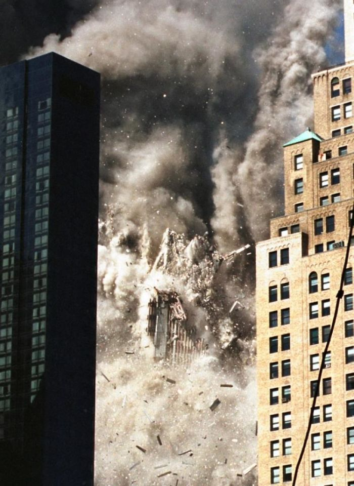 1 - 9/11 photo of the tower coming down framed between 2 buildings in the foreground