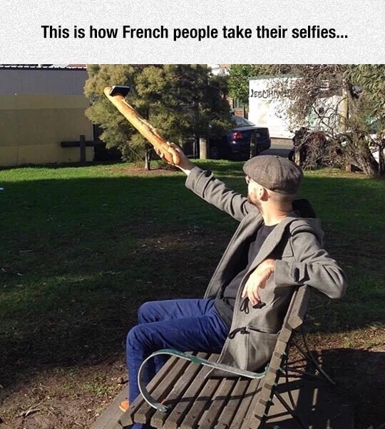 21 - French person taking a selfie using a baguette to hold up the phone.
