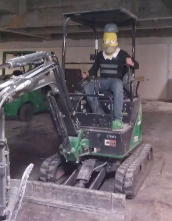 14 - Someone driving a track backhoe wearing a Homer Simpsons mask.