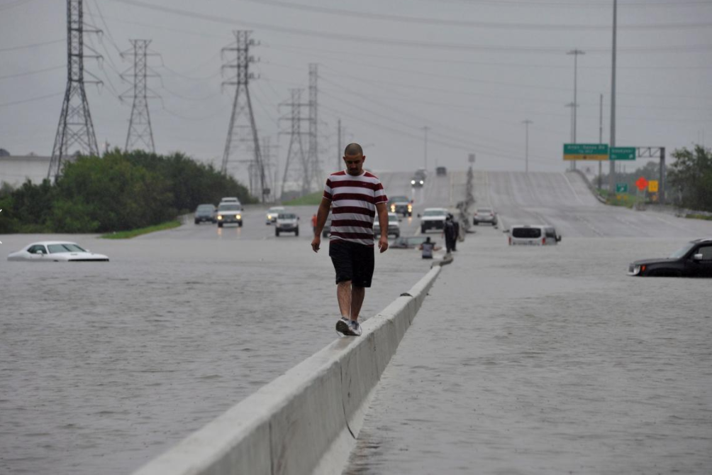7 - Man walks on highway divided to stay dry in aftermath of Hurricane Harvey