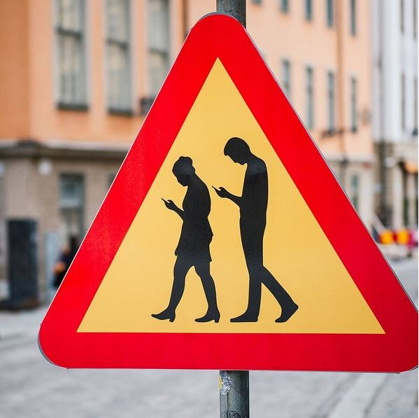 9 - A road sign warns drivers that they may encounter pedestrians who are deeply absorbed in their smartphones, in Stockholm, Sweden