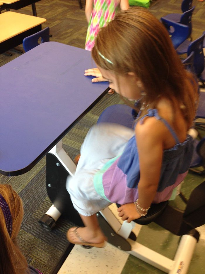 Elementary school classroom has desk with pedals so kids can move around while learning.
