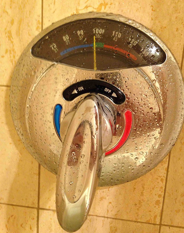 Shower handle with a thermometer for water temperature.