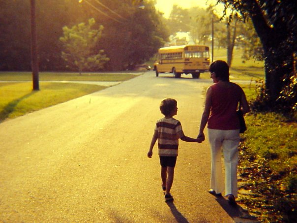 19 - Kid walking home with mom, holding hands, and school bus drives off in the distance.