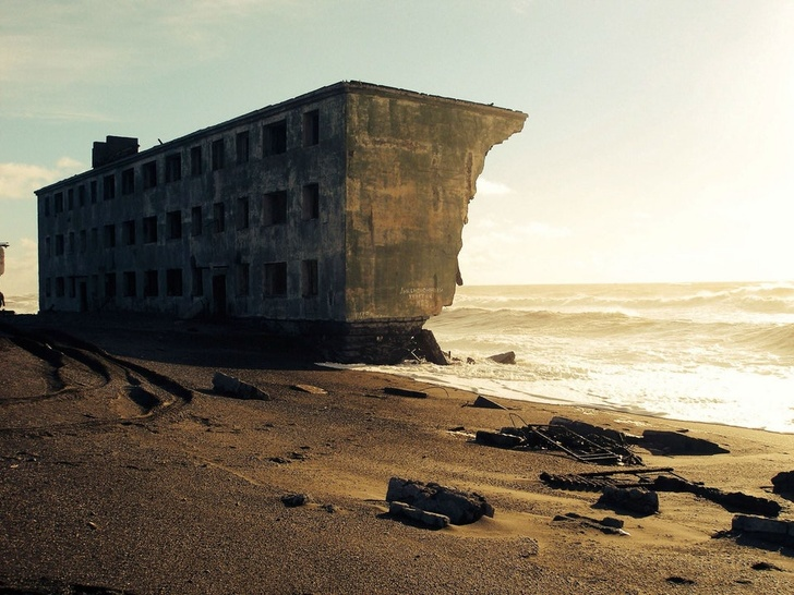 31 - An abandoned apartment building being claimed by the sea in the former fishing village of Kirovsky, Russia