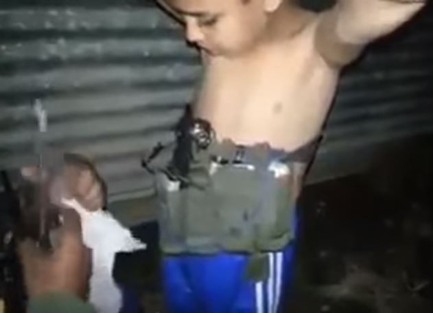 7 - Iraqi soldier removes suicide belt from boy in Mosul