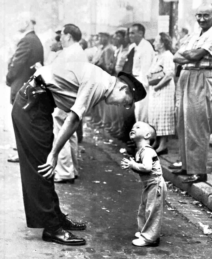 10 - A policeman politely stops a little boy from crossing the street in front of parade, 1958.